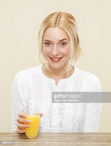 smiling female with glass of fresh orange juice