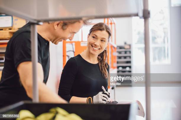 smiling female worker looking at colleague while discussing over document in warehouse - 40 44 years woman caucasian stock pictures, royalty-free photos & images
