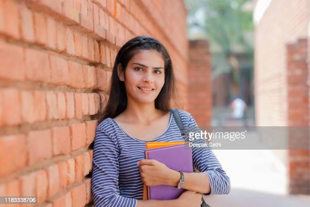 smiling female young college student of indian ethnicity stock photo - one teenage girl only stock pictures, royalty-free photos & images