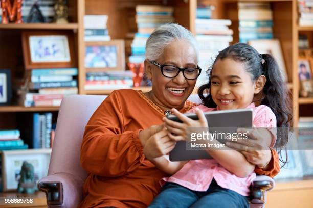 smiling females using digital tablet at home - grandparent stock pictures, royalty-free photos & images