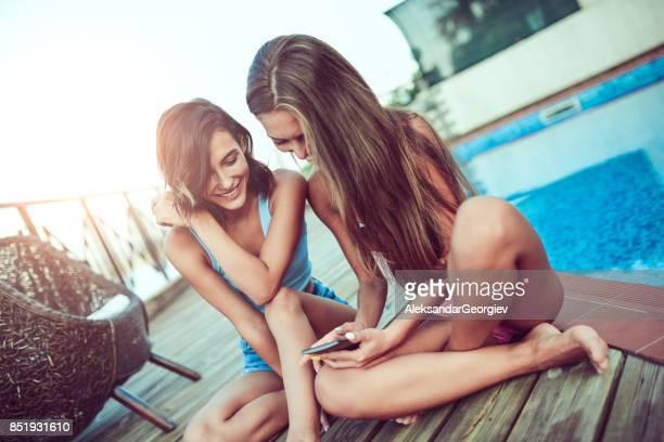 femelles souriantes je regarde des photos drôles sur smartphone par piscine - teen webcam photos et images de collection