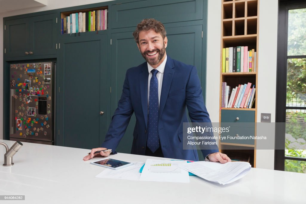 Smiling financial advisor with digital tablet and paperwork in kitchen : Stock Photo
