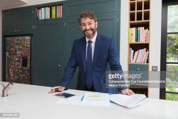 smiling financial advisor with digital tablet and paperwork in kitchen - 紺色 ストックフォトと画像