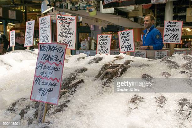 A smiling fish monger stands behind iced black cod ling cod and tilapia at a stand in Pike Place Market in Seattle Washington