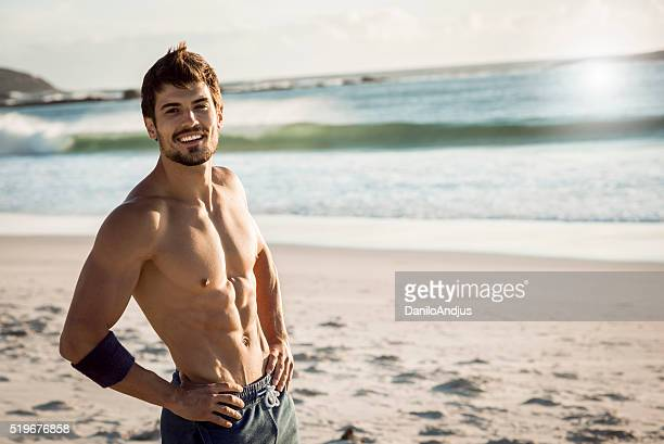 smiling fit man relaxing after workout - muscle stock pictures, royalty-free photos & images