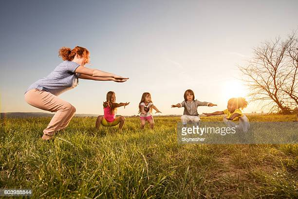 Smiling fitness instructor and children doing squats at sunset.