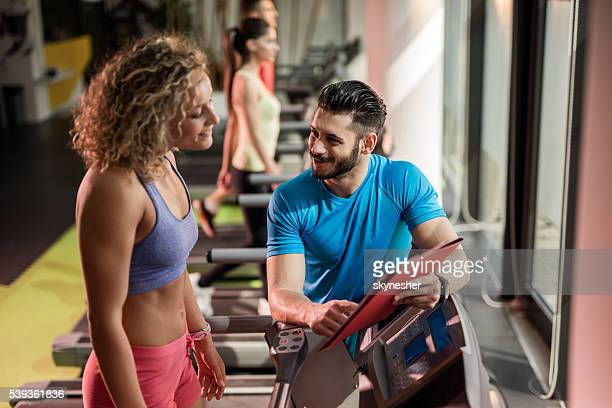 Smiling fitness instructor assisting young woman in a gym.