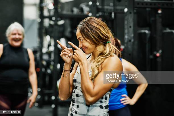 smiling fitness instructor encouraging class during workout in gym - dansstudio stock pictures, royalty-free photos & images