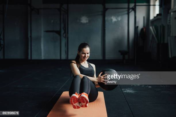 smiling fitness woman doing exercises with the medicine ball on the mat - medicine ball stock pictures, royalty-free photos & images