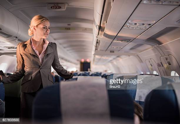 Smiling flight attendant on duty in the airplane.