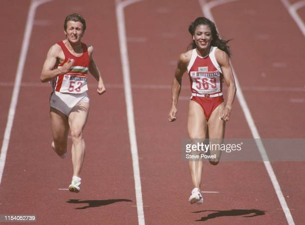 Smiling Florence Griffith-Joyner of the United States passes Nataliya Pomoshchnikova-Voronova of the Soviet Union on her way to winning gold in the...