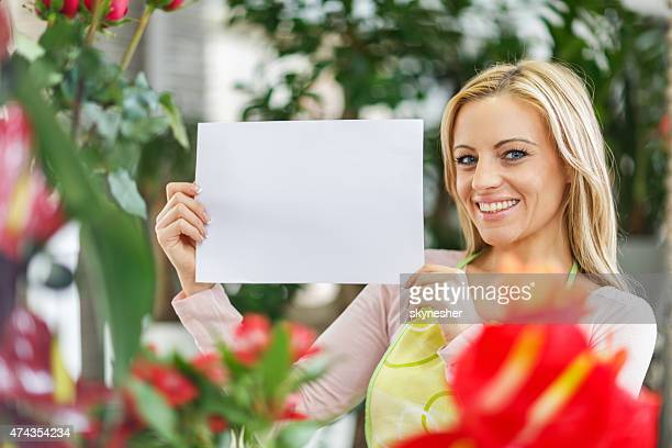 smiling florist hold blank sign and looking at camera. - person holding blank sign stock pictures, royalty-free photos & images