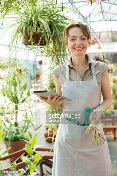 Floreria sonriente sosteniendo la tableta digital y guante de trabajo