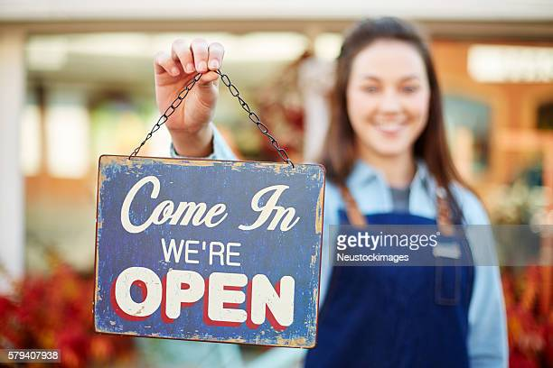 Smiling florist holding up sign saying come in we're open