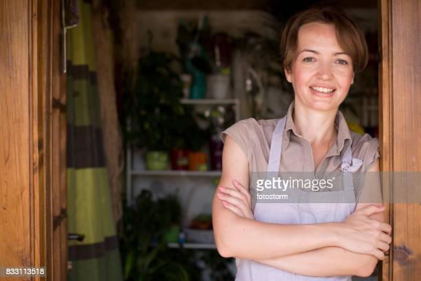 lächelnd blumengeschäft blumen shop eingang - frauen über 30 stock-fotos und bilder