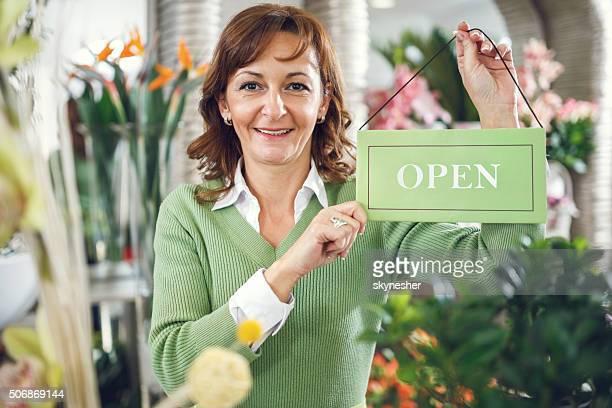 Sonriendo florista en la floristería retención señal de abierto.