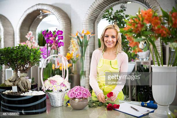 Smiling florist making bouquet of roses and looking at camera.
