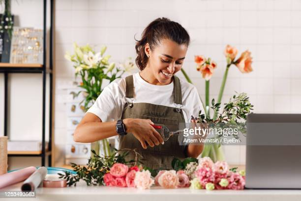 smiling florist working in shop - bunch of flowers stock pictures, royalty-free photos & images