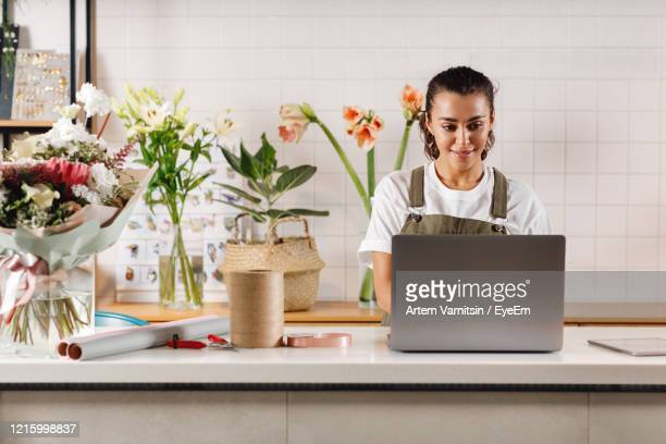 smiling florist working on laptop at checkout counter in shop - small business stock pictures, royalty-free photos & images