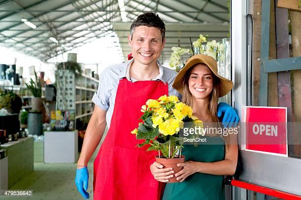 Souriant fleuriste dans leur magasin