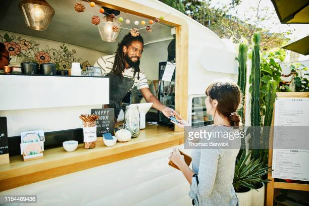 smiling food truck owner taking credit card for payment from customer - food truck fotografías e imágenes de stock
