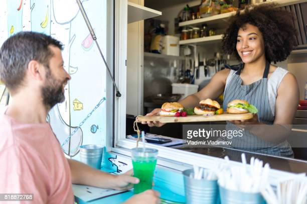 Glimlachend voedsel van werknemer aanbod broodjes