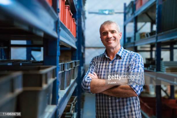 smiling foreman with arms crossed in warehouse - waist up stock pictures, royalty-free photos & images