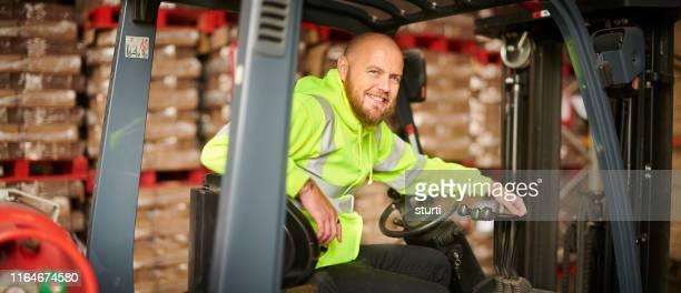 lächelnder gabelstaplerfahrer - berufsfahrer stock-fotos und bilder