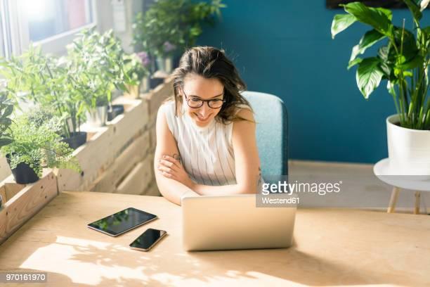 Smiling freelancer sitting at desk in loft looking at laptop