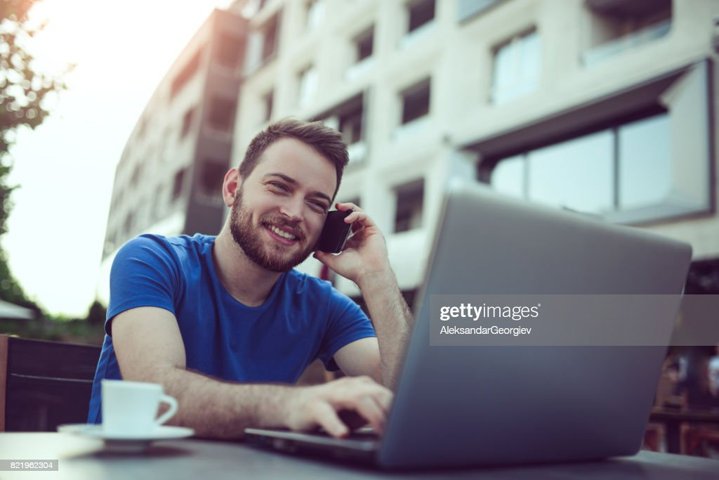 Smiling Freelancer Working and Talking on the Phone at his Favorite Coffee Place : Stock Photo