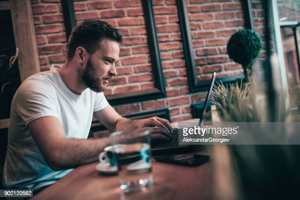 smiling freelancer working at his favorite coffee place - adult movies stock pictures, royalty-free photos & images