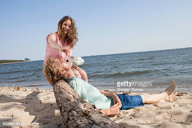 Smiling friend feeding cherry to young man while relaxing at beach