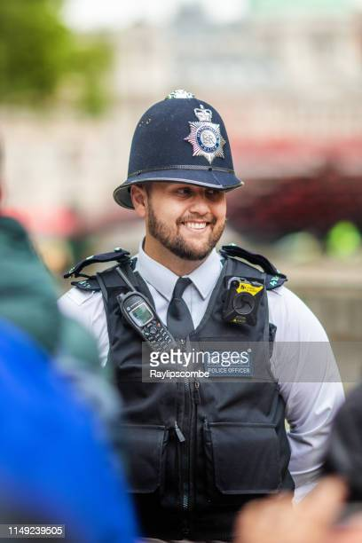 smiling friendly metropolitan policeman engaging with crowds in westminster, central london - metropolitan police stock pictures, royalty-free photos & images