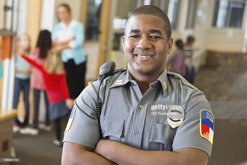 Smiling friendly police officer providing security on school campus : Stock Photo