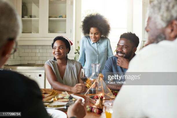 smiling friends and family talking at home - family dinner stock pictures, royalty-free photos & images