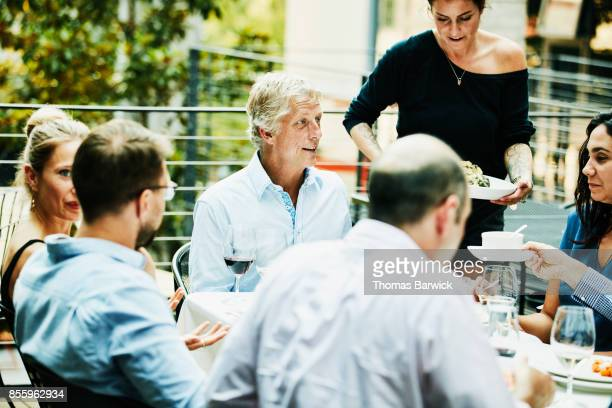 Smiling friends being served food during celebration dinner on restaurant patio