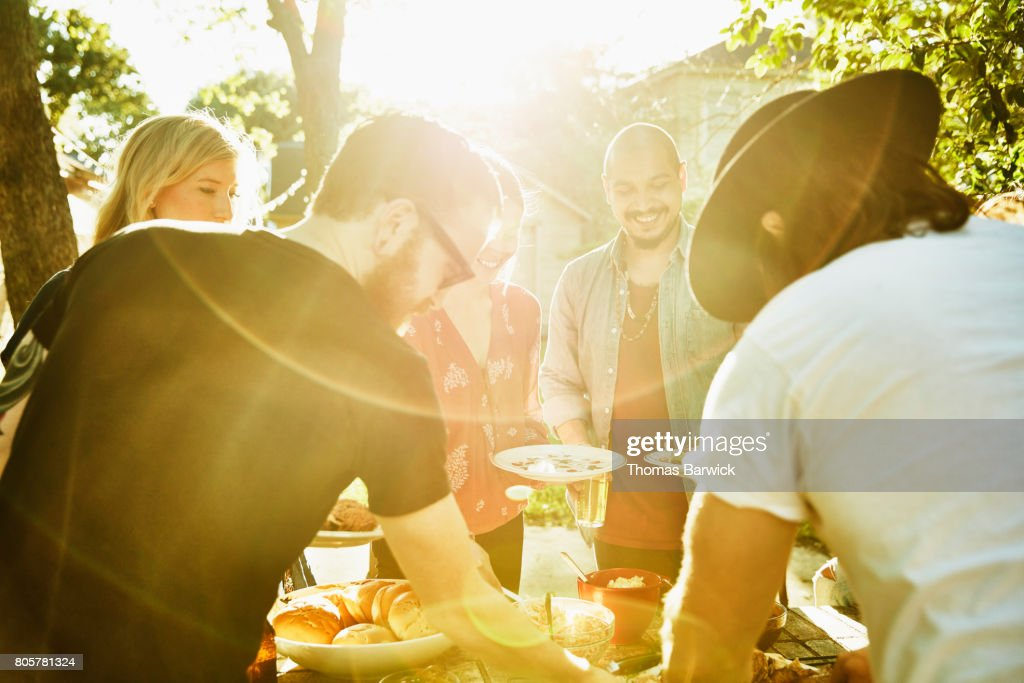 Smiling friends dishing up food in backyard on summer evening : Stock Photo