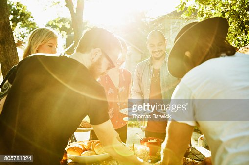 Smiling friends dishing up food in backyard on summer evening