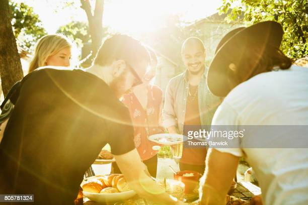 smiling friends dishing up food in backyard on summer evening - outdoor party stock pictures, royalty-free photos & images