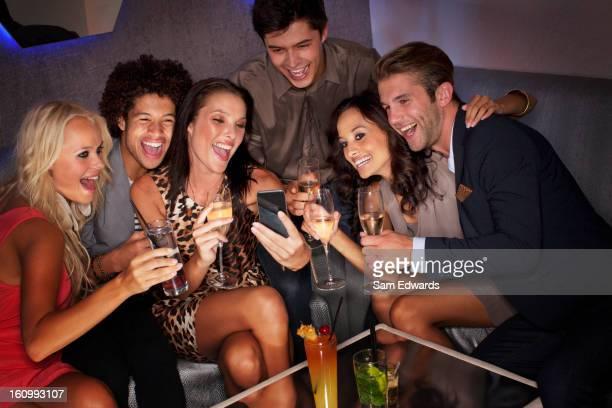 Souriant amis boire des cocktails et en regardant vers le bas