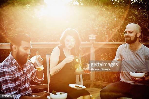 Smiling friends eating dinner on backyard deck