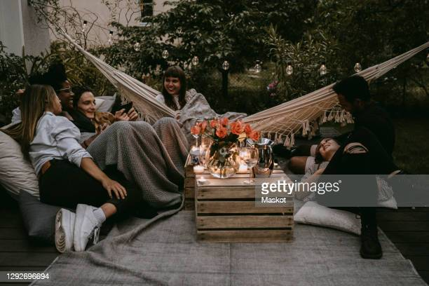smiling friends enjoying at social gathering in yard during sunset - garden party stock pictures, royalty-free photos & images