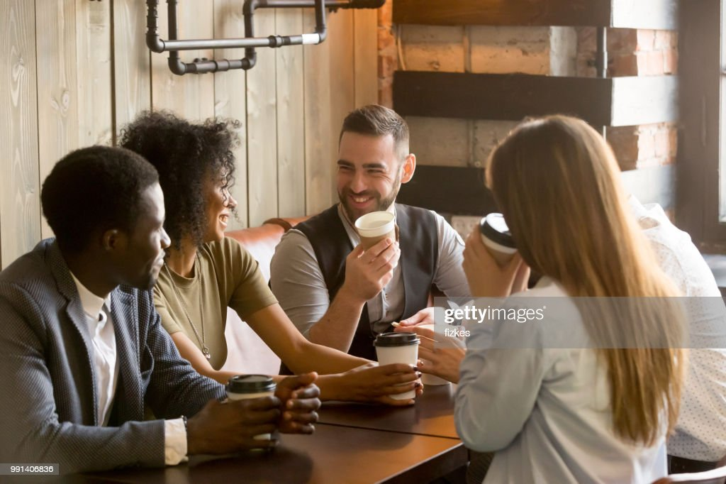 Smiling friends enjoying time together having coffee in cafe : Stock Photo
