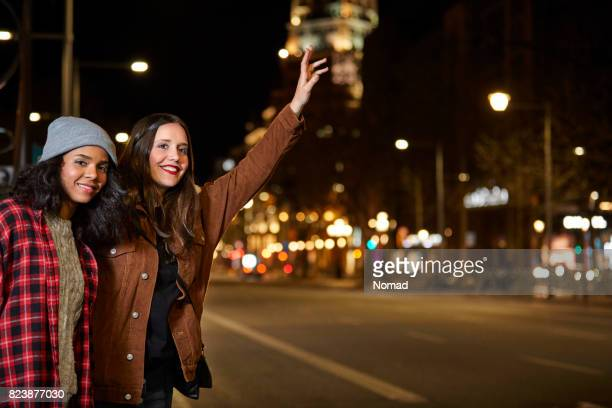 夜に道端でタクシーを呼んで友達に笑顔