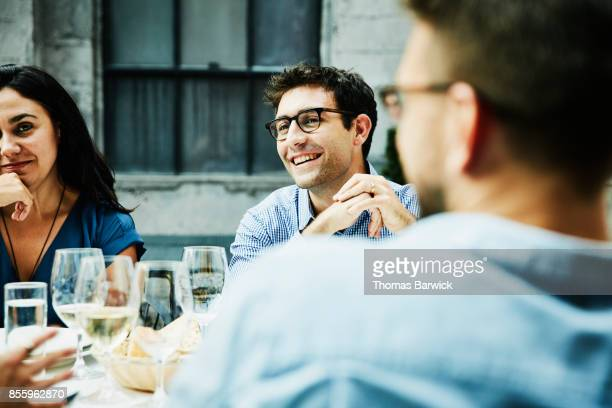 Smiling friends hanging out during dinner on outdoor patio