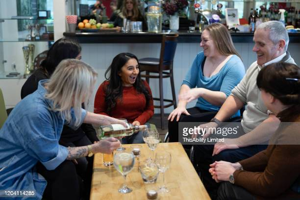 smiling friends having drinks in restaurant - medium group of people stock pictures, royalty-free photos & images