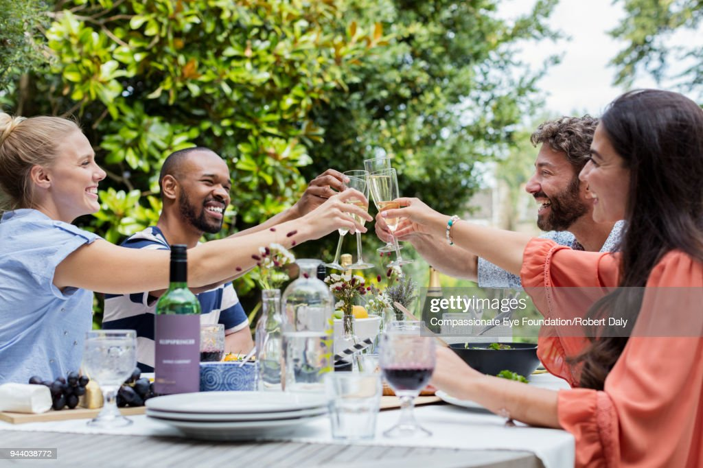 Smiling friends having lunch toasting with champagne glasses on garden patio : Stock Photo