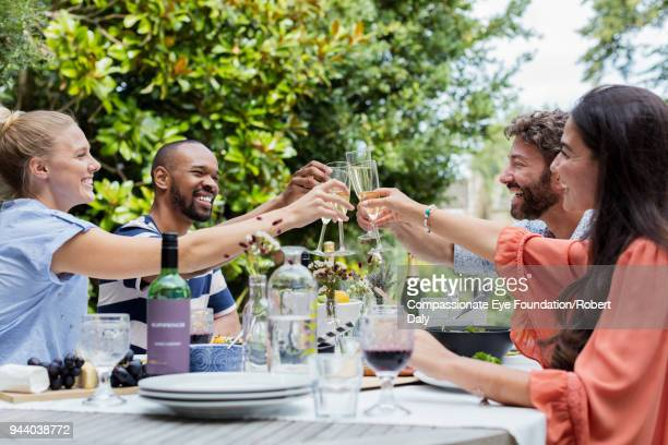Smiling friends having lunch toasting with champagne glasses on garden patio