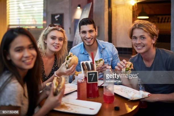 Amigos sonrientes con hamburguesas en restaurante