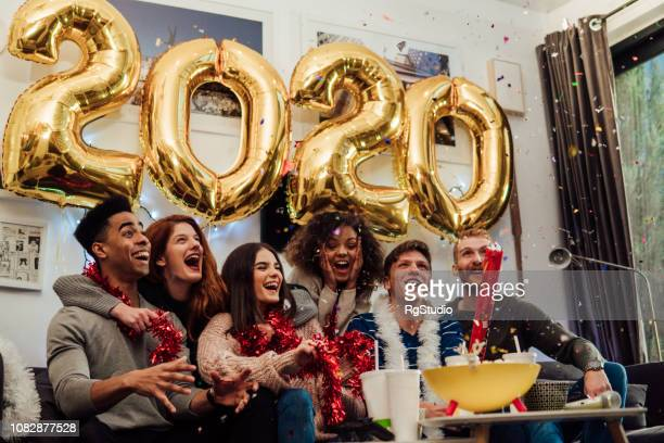 smiling friends holding confetti box - new year's day stock pictures, royalty-free photos & images